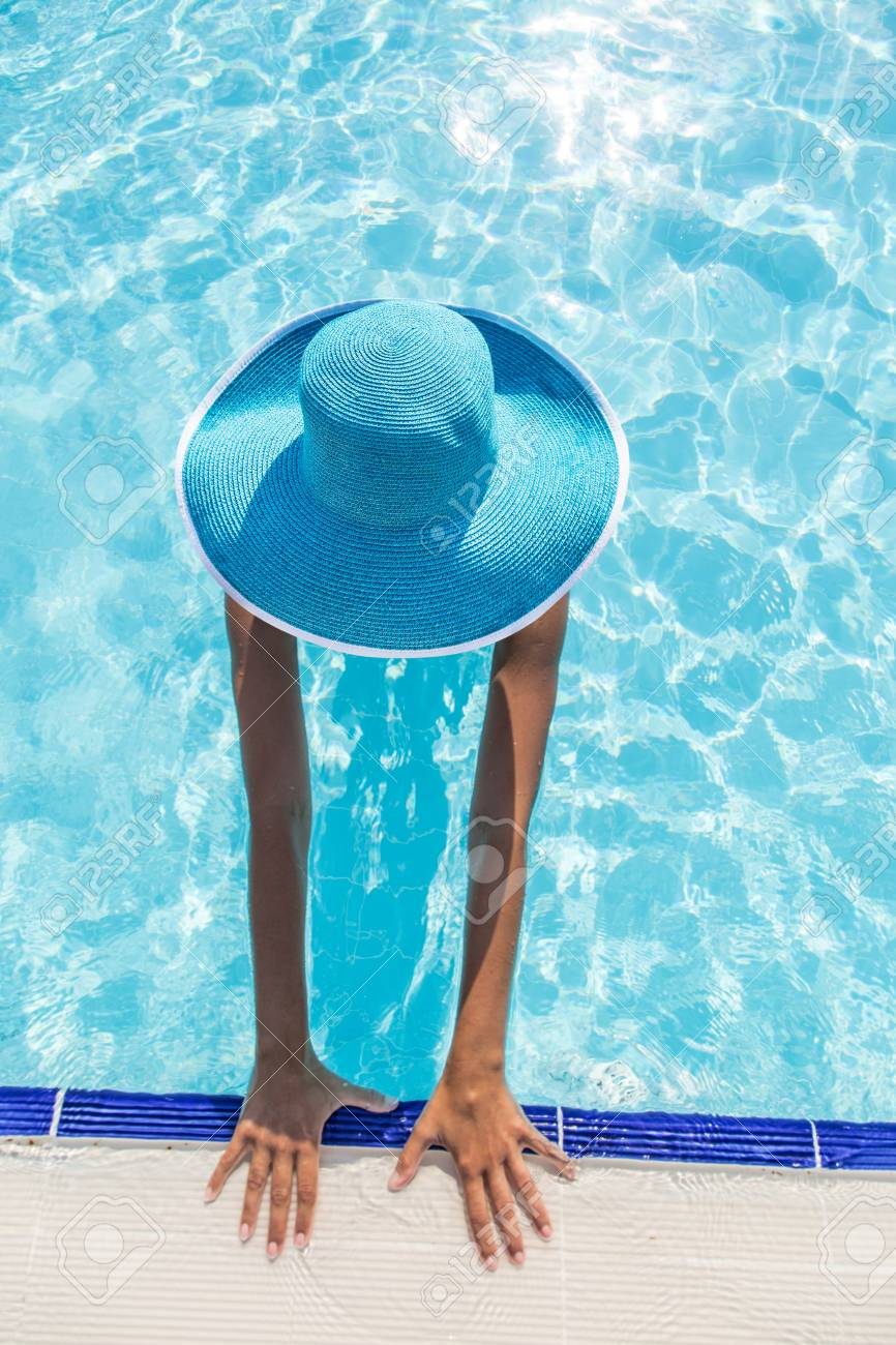 Woman In Sun Hat In The Swimming Pool. Top View. Stock Photo ... b04e08f9a46