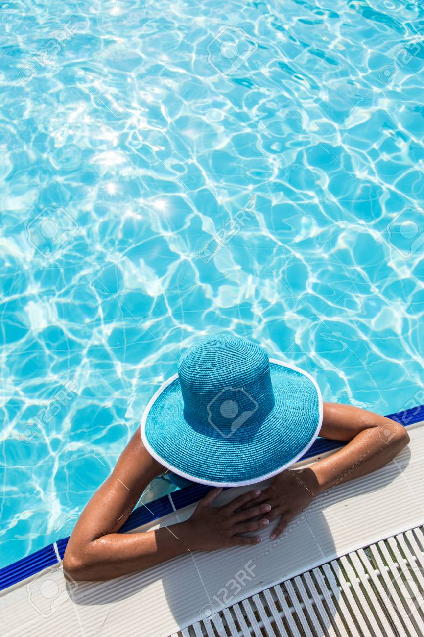 520d528b4 Woman in sun hat in the swimming pool. Top view.