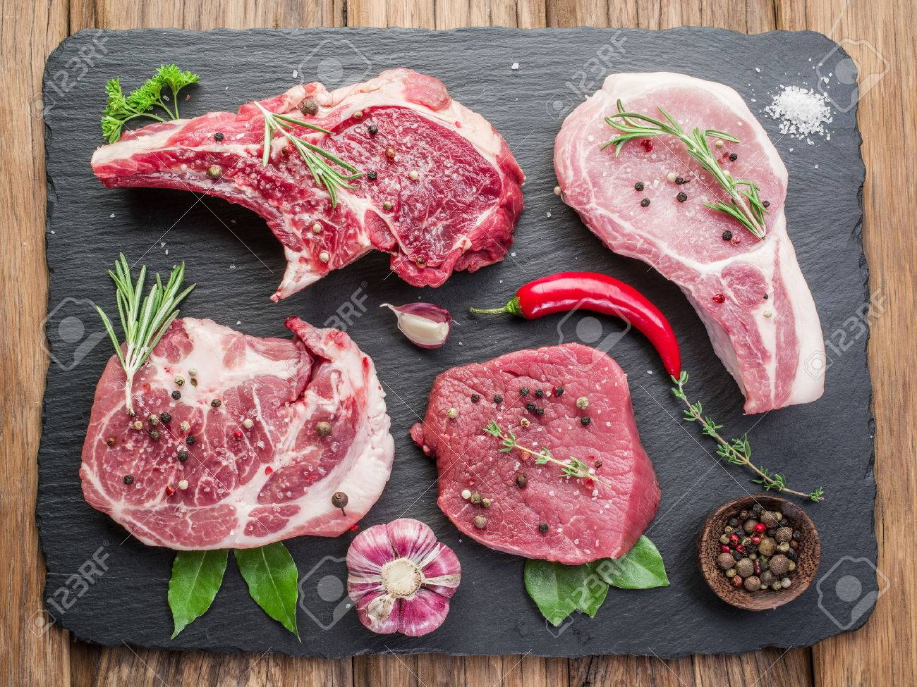 Raw meat steaks with spices on the black cutting board. Standard-Bild - 56782259