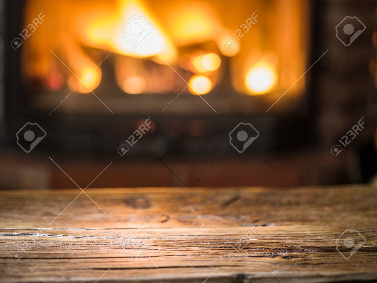 Old wooden table and fireplace with warm fire on the background. Standard-Bild - 60157462