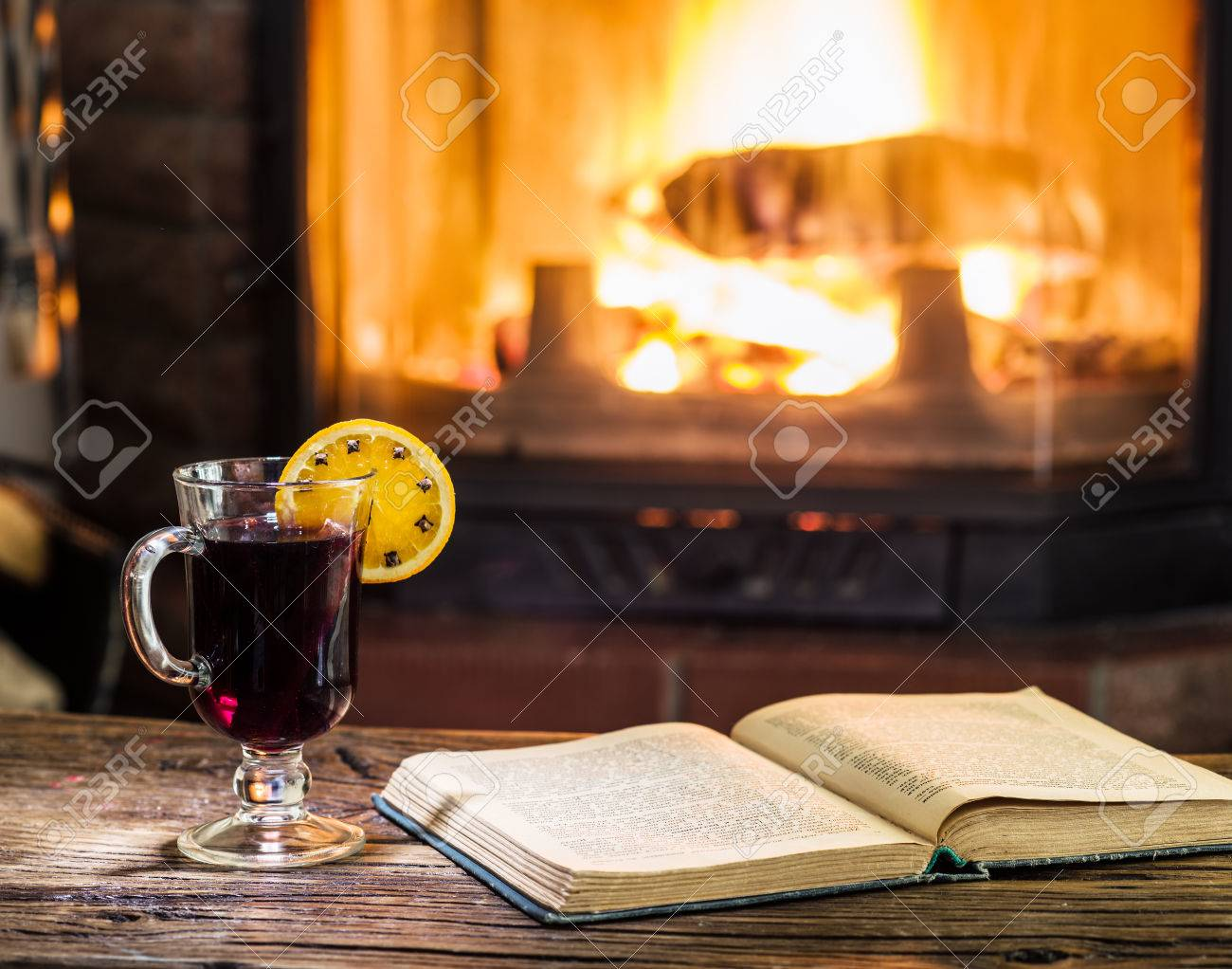 Hot Mulled Wine And A Book On The Wooden Table Fireplace With