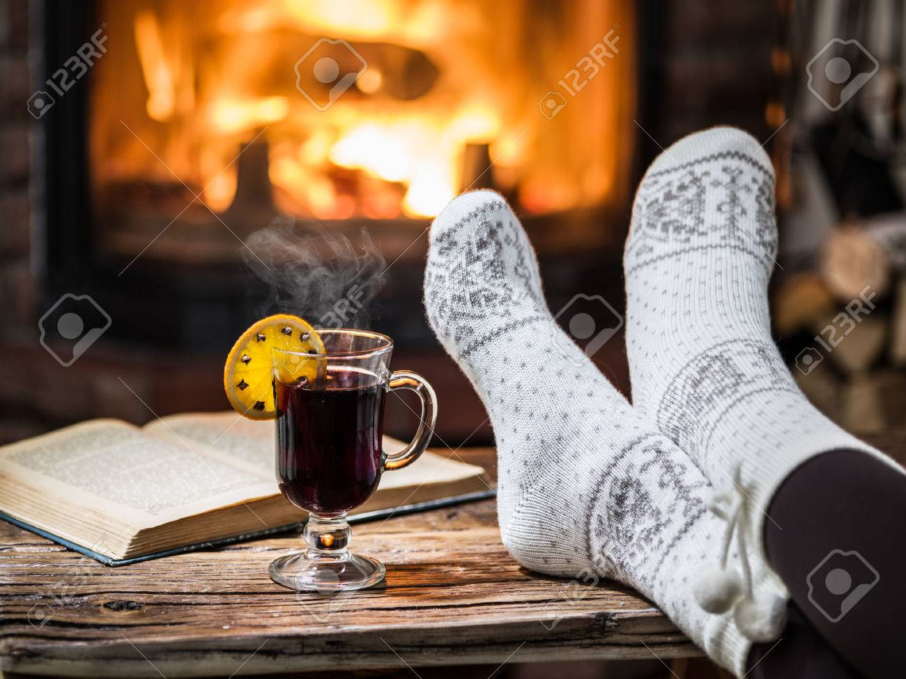 Warming and relaxing near fireplace. Woman feet near the cup of hot wine in front of fire. Standard-Bild - 63146140
