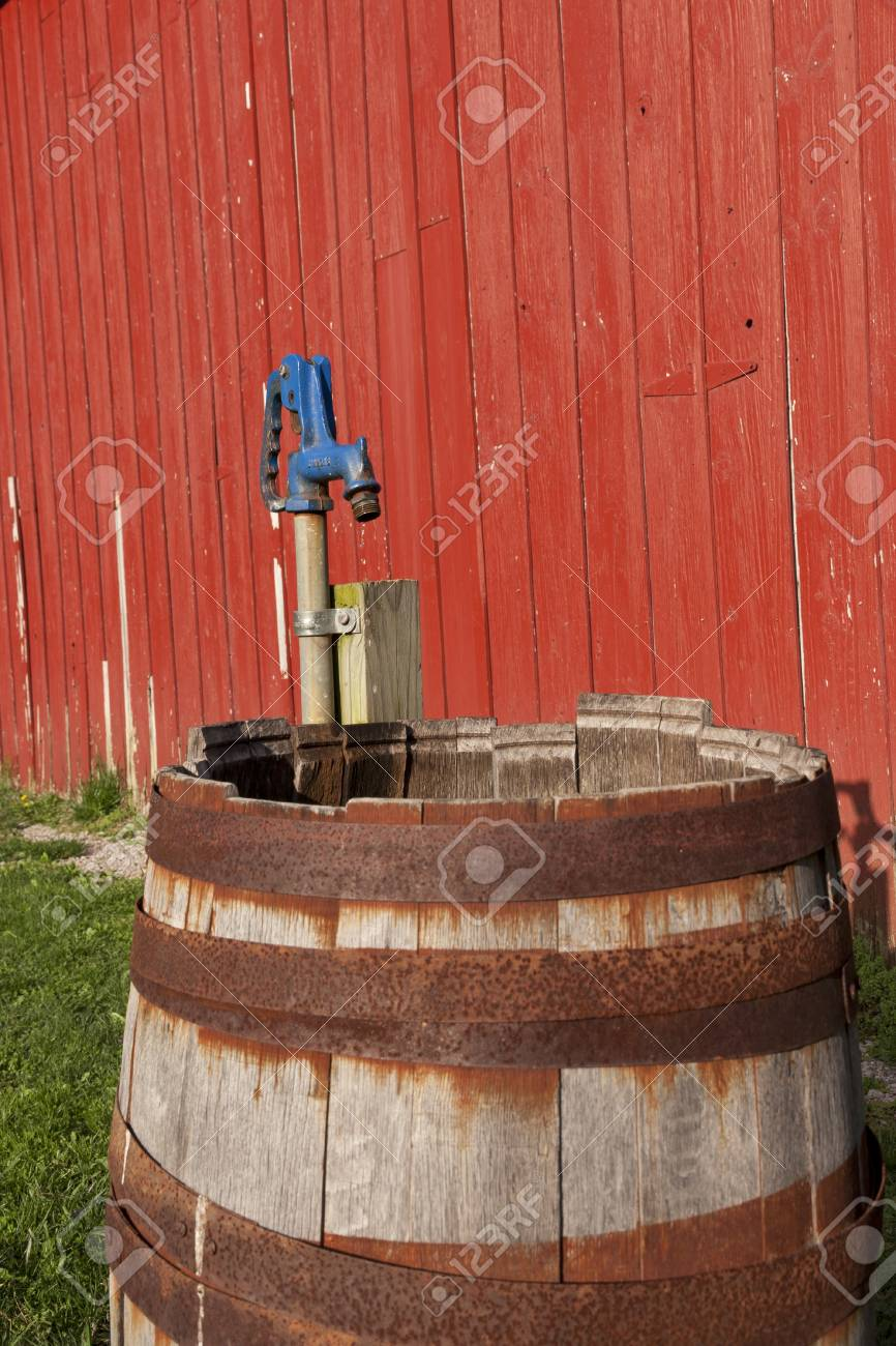 Old wooden barrel with water pump beside a red barn