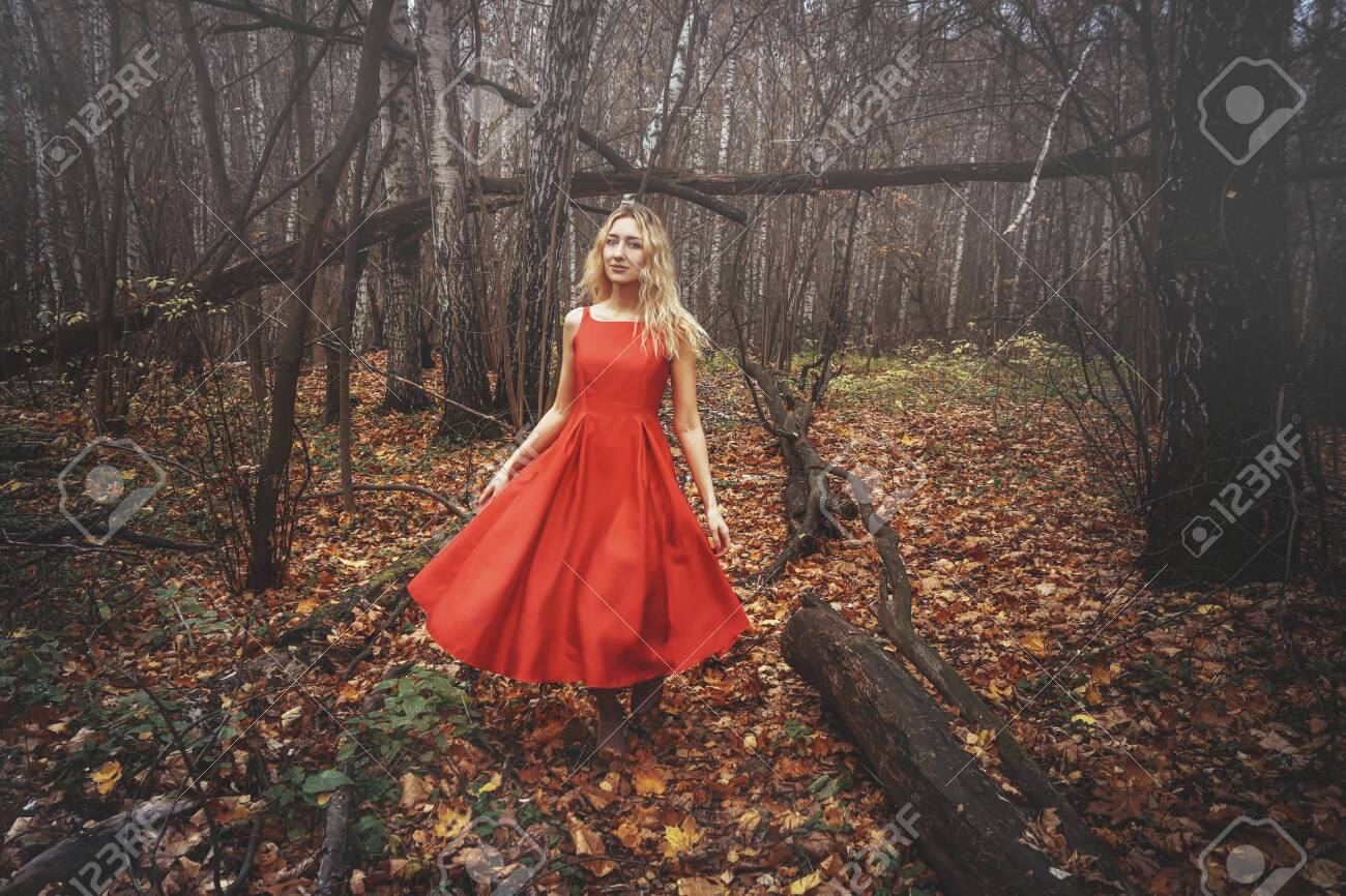 Young pretty woman in the red dress is walking in the foggy mystical forest with fallen leaves - 133447528