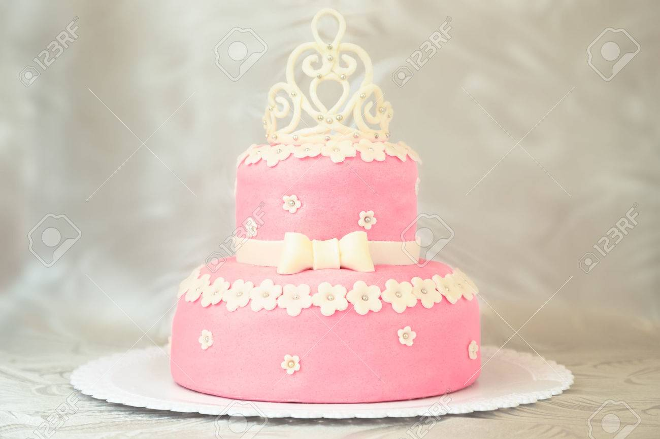 Pink Cake With A Crown On A White Plate Over A White Tablecloth ...