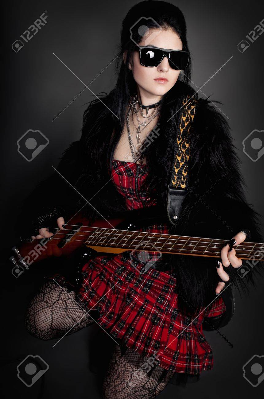 series. Fashion style photo of young rocked woman in studio  with guitar Stock Photo - 12378452