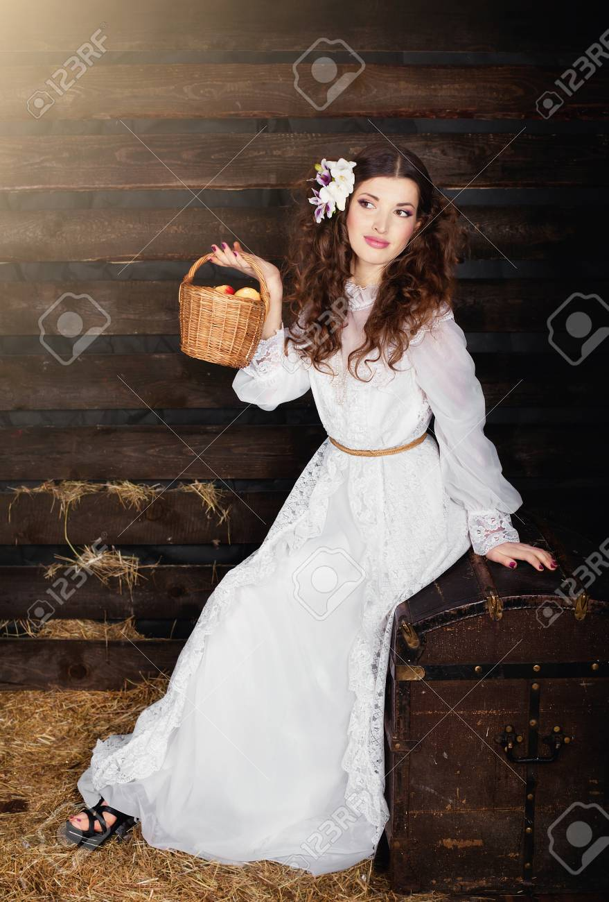 The woman in a long white dress with a wattled basket in hands on a mow Stock Photo - 12704137
