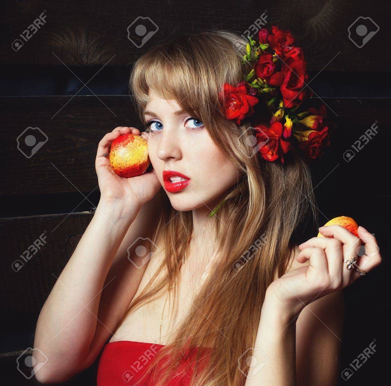 woman in a red dress with an apple in hands on a mow Stock Photo - 14642372