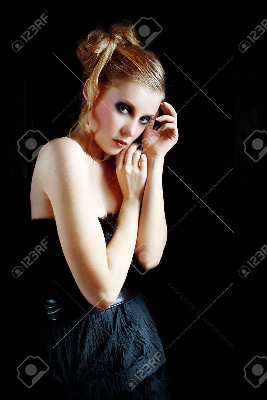 Fashion model wearing black dress over the dark interior hall Stock Photo - 10347682