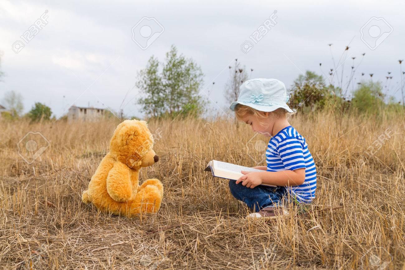 Cute girl reading book Teddy bear on the grass. - 45662441