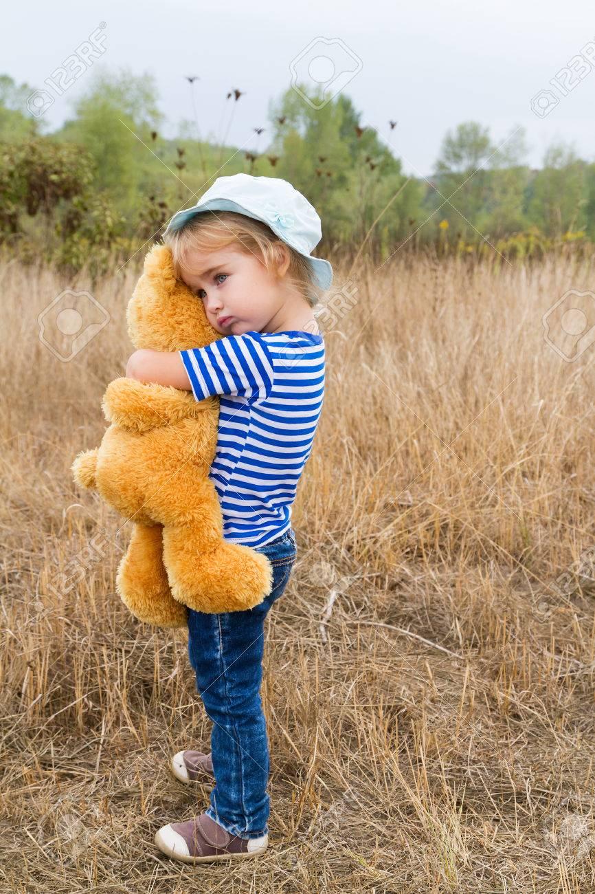 Cute little girl standing in the grass hugging a Teddy bear - 45662445