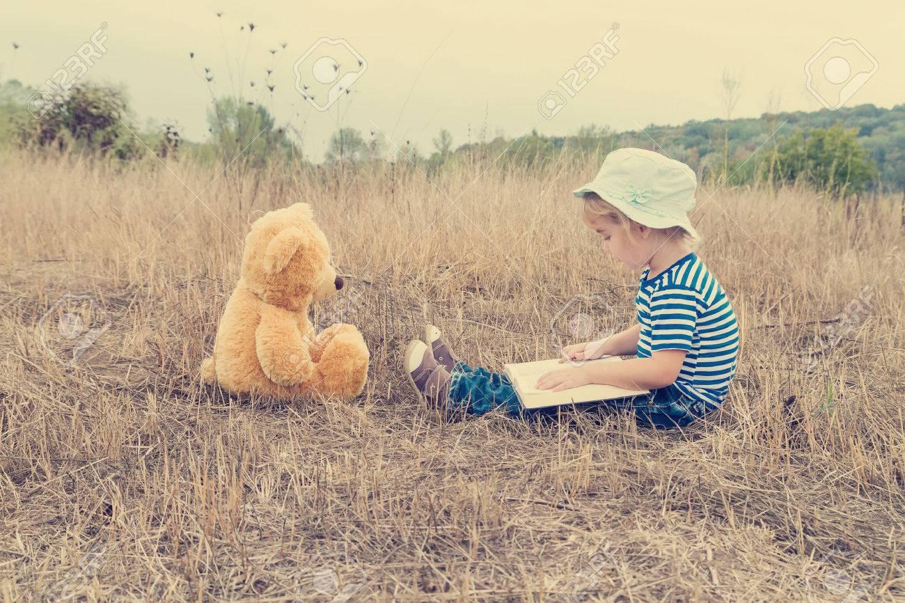 Cute girl reading book Teddy bear on the grass. - 49063016