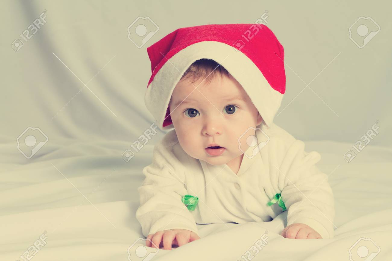 c7c4d724d Cute happy newborn baby in christmas hat lying on bed