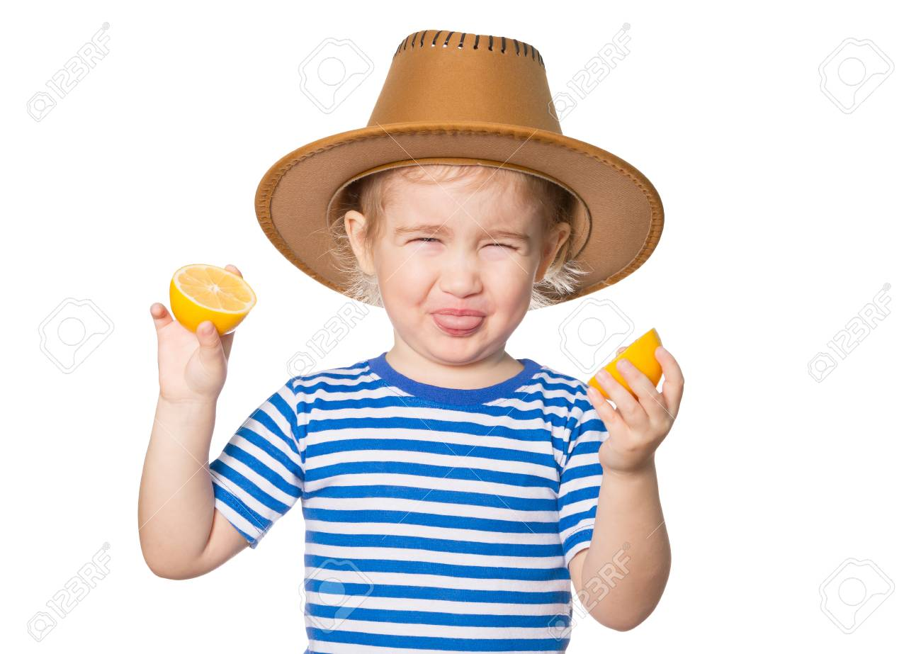 Little Funny girl in striped shirt and hat keeps lemons. Isolated on white background - 50884722