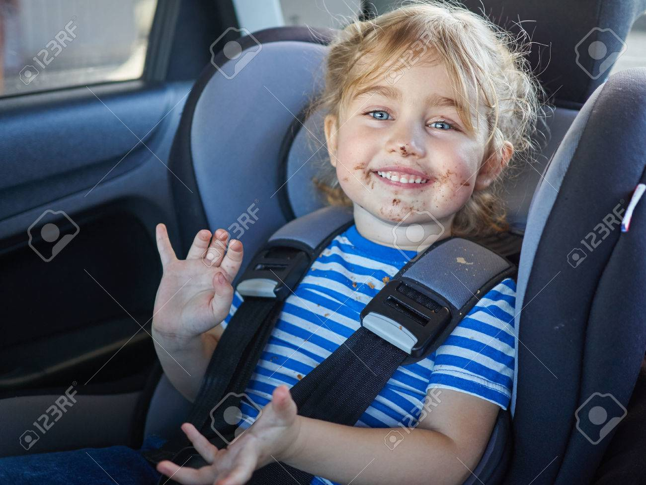 Little dirty girl , baby in a safety car seat. Safety and security - 53131185