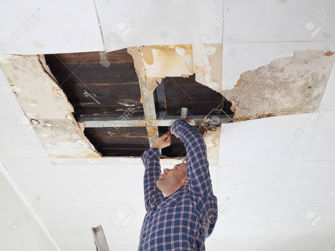 Man repairing collapsed ceiling. Ceiling panels damaged huge hole in roof from rainwater leakage.Water damaged ceiling . - 55750277