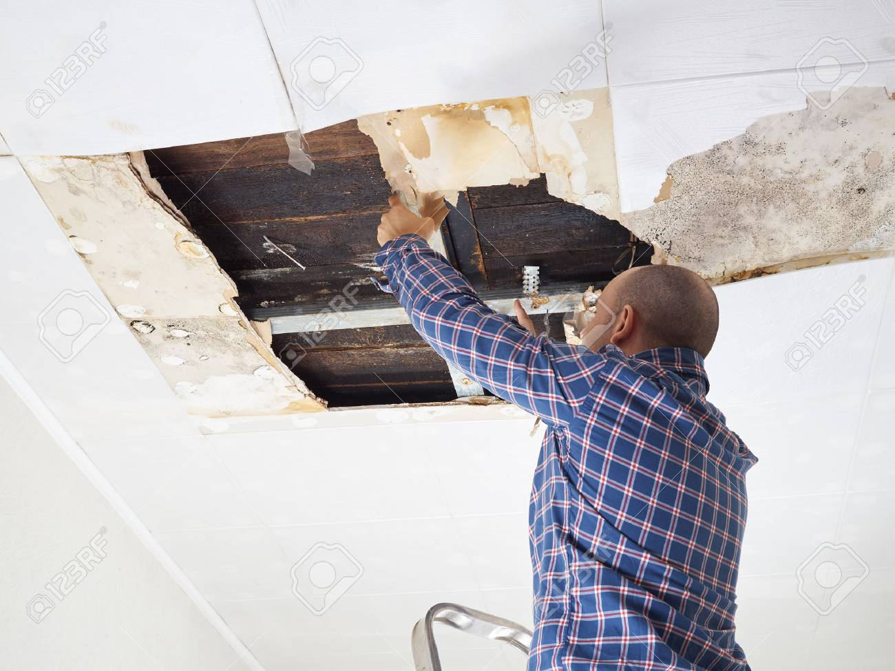 Man repairing collapsed ceiling. Ceiling panels damaged huge hole in roof from rainwater leakage.Water damaged ceiling . - 57035834