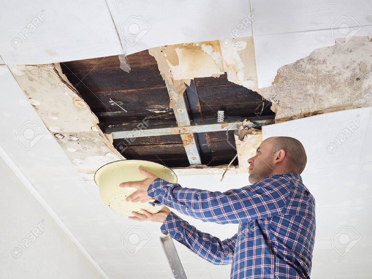 Man Collecting Water In basin From Ceiling. Ceiling panels damaged huge hole in roof from rainwater leakage.Water damaged ceiling . - 57035838