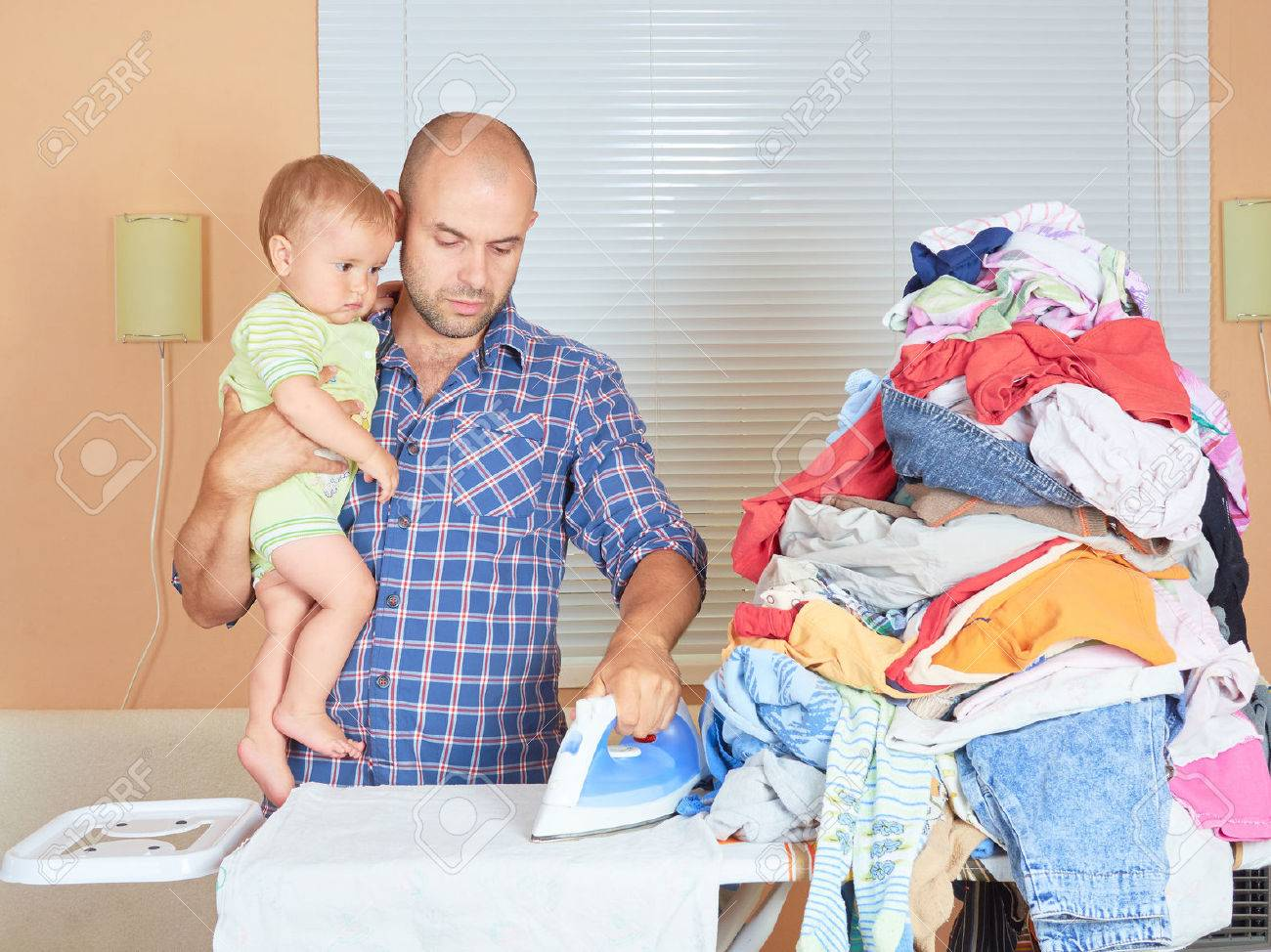 Caucasian man father and son in his hands, ironed clothes in the room near the window. Homework. - 59949789
