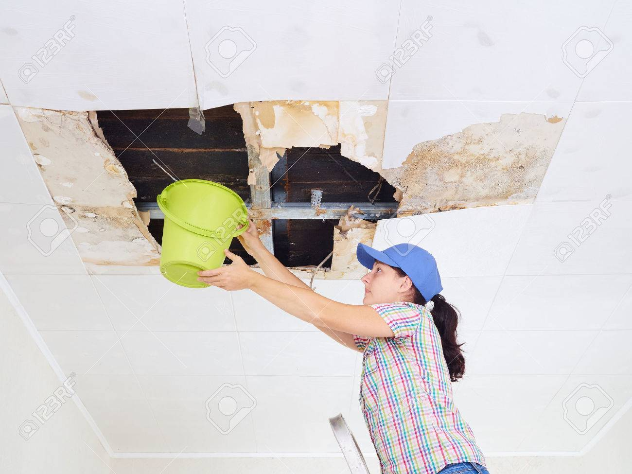 Young Woman Collecting Water In Bucket From Ceiling. Ceiling panels damaged huge hole in roof from rainwater leakage.Water damaged ceiling . - 66447462