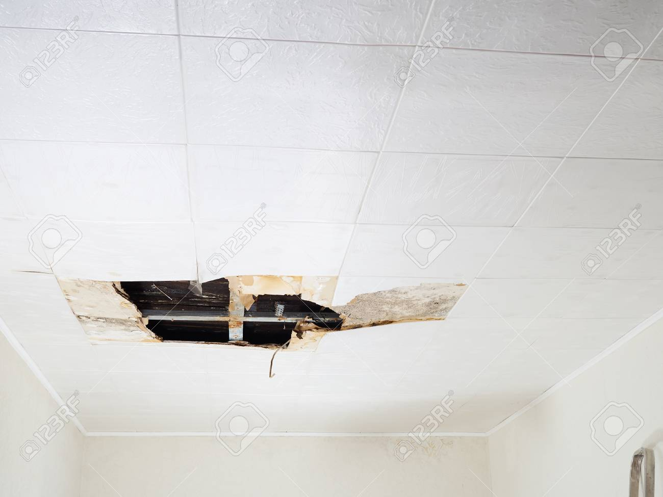 Ceiling panels damaged huge hole in roof from rainwater leakage.Water damaged ceiling . - 89869843