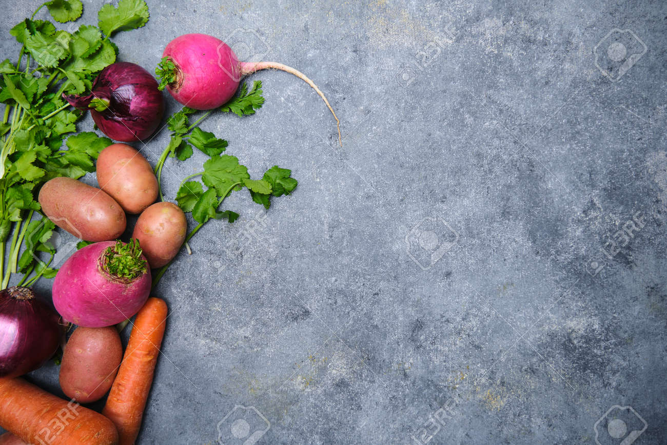 Turnip, cilantro, potatoes, carrots and red onions on a dark background - 167903902