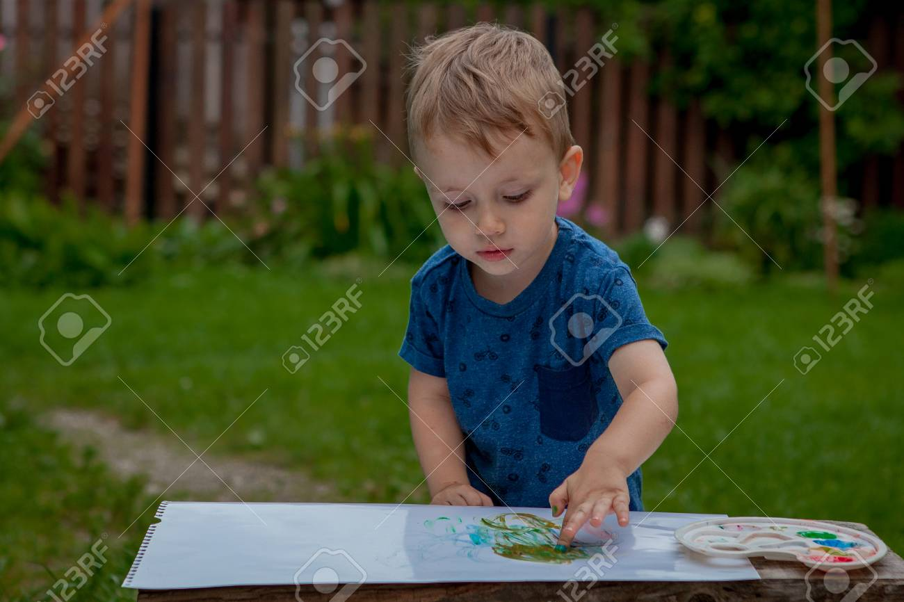 Cute little boy painting with a paint hands using gauche paints. - 107013180