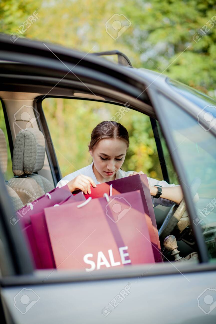 Woman with her shopping bags into the car - shopping concept - 128687021