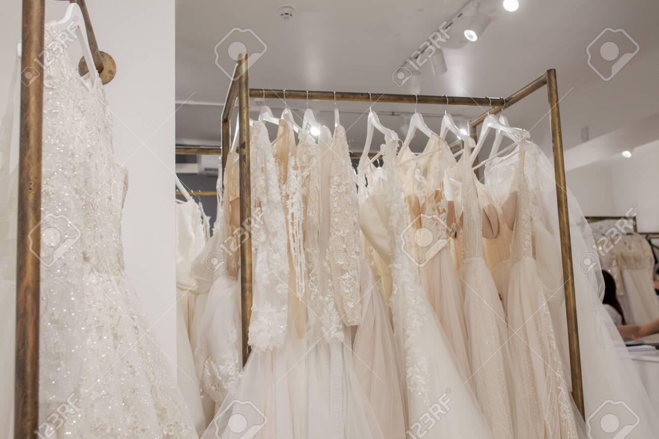 Assortment of dresses hanging on a hanger on the background studio. Fashion wedding trends. Interior of wedding shop. - 129849022