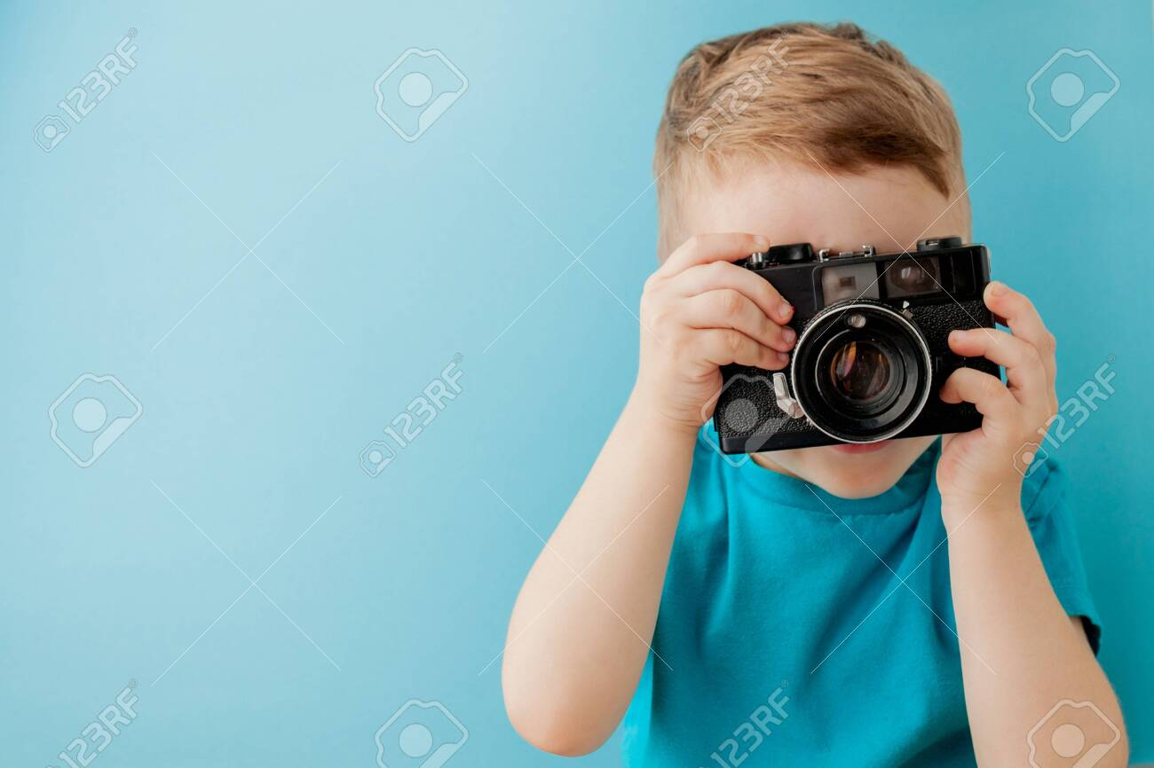 Little boy with an old camera on a blue background. - 134684475