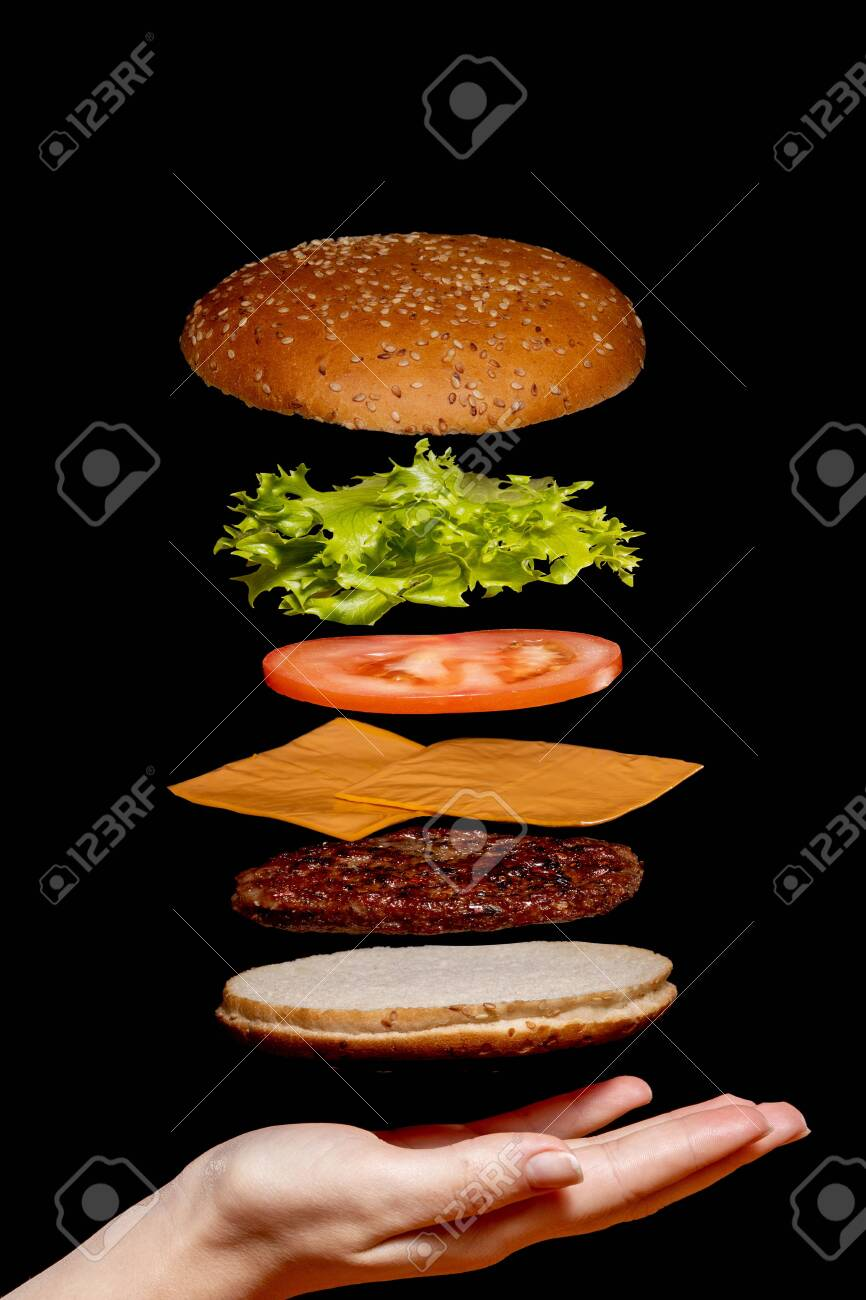 Flying ingredients burger or cheeseburger on a small wooden cutting board isolated on a dark background. Burger floating in the air above the table. Space for text. - 145875527