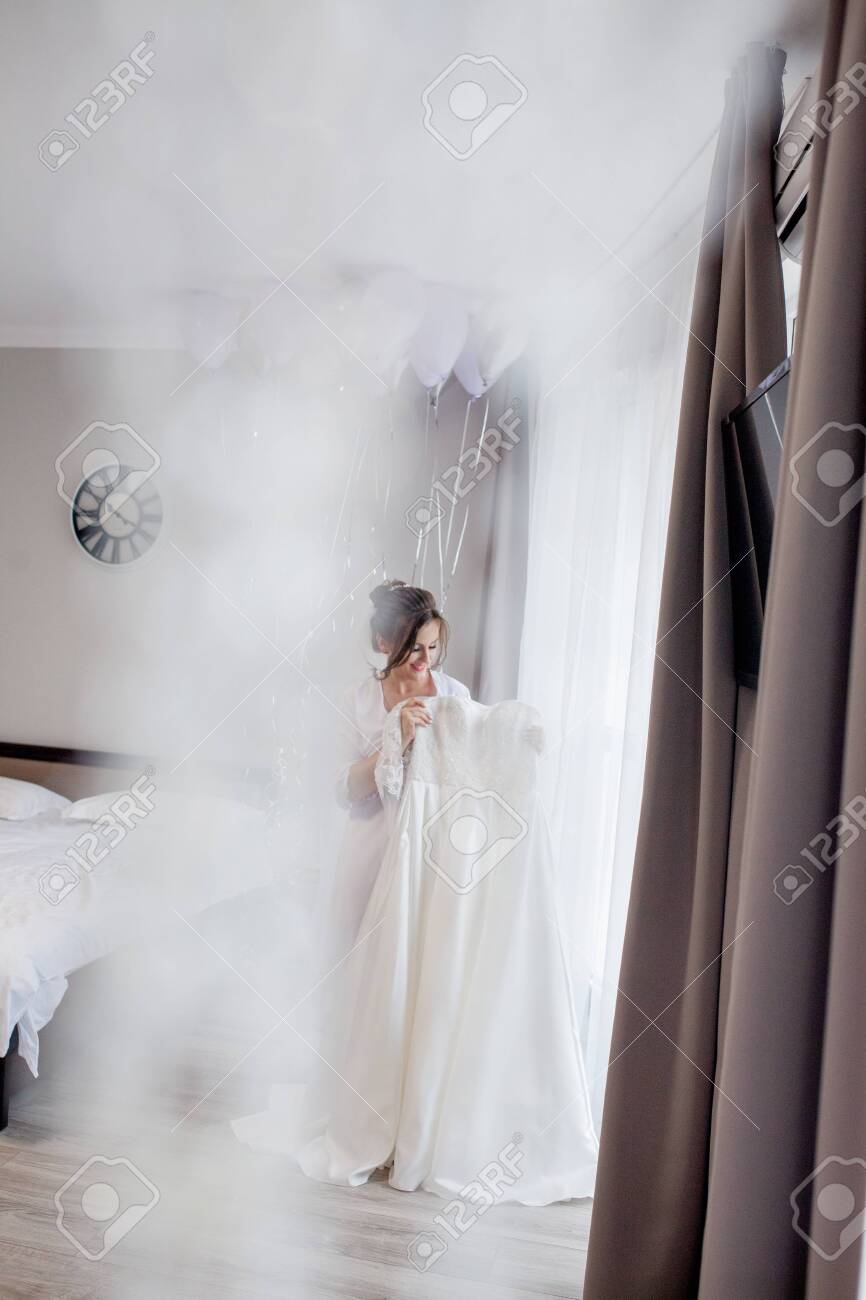 Young Woman In Silk Bathrobe Touching Her Wedding Dress And Smiling Stock Photo Picture And Royalty Free Image Image 150474665