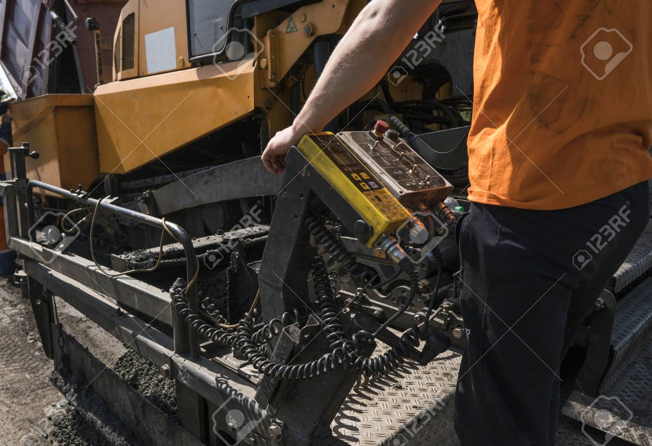 Worker operating asphalt paver machine during road construction and repairing works. A paver finisher, asphalt finisher or paving machine placing a layer of asphalt. Repaving - 104507904