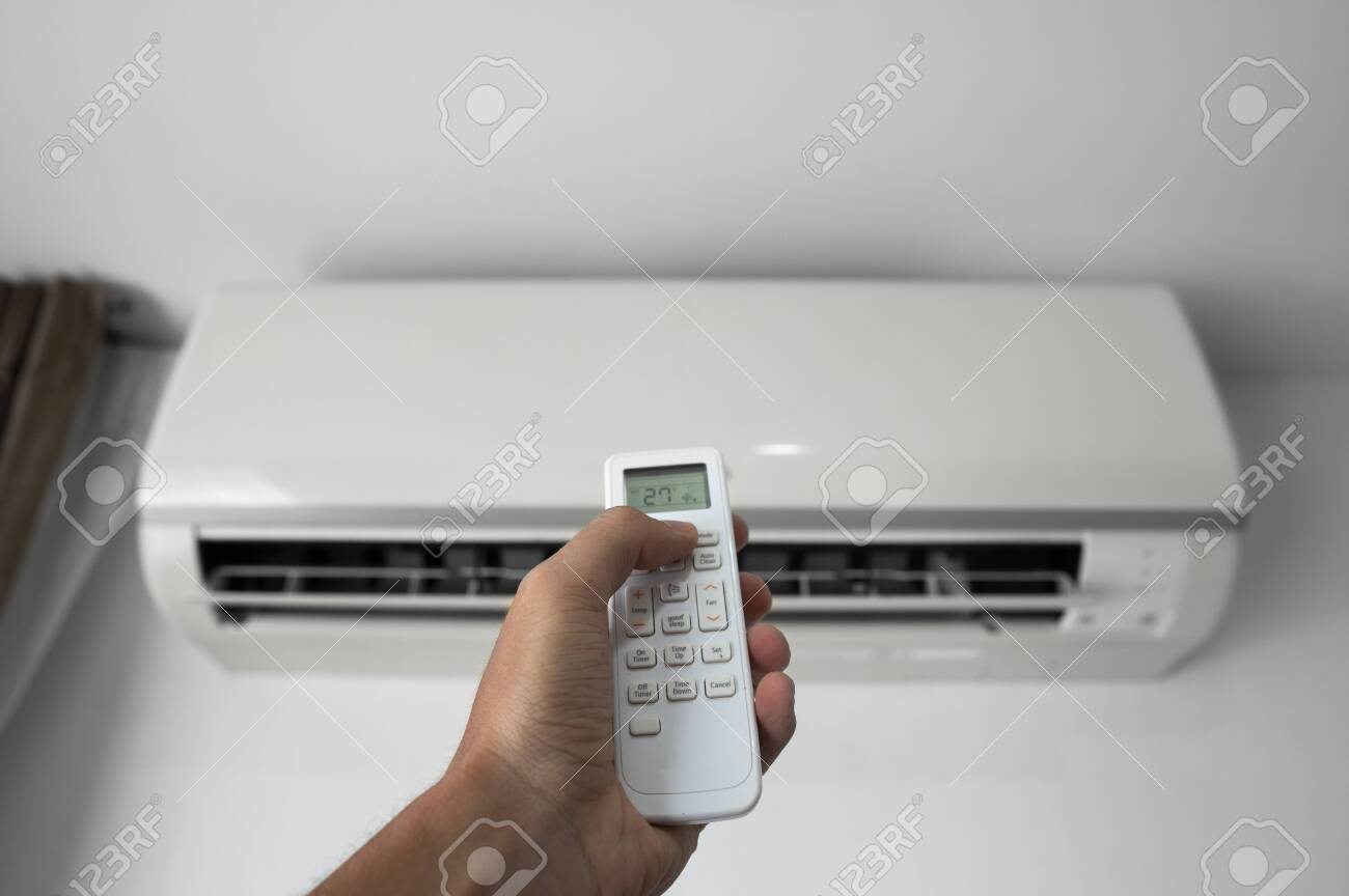 Mans hand using remote controler. Hand holding rc and adjusting temperature of air conditioner mounted on a white wall. Indooor comfort temperature. Health concepts and energy savings. - 129225437