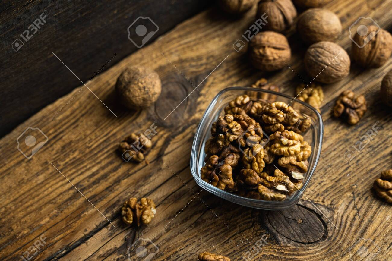 Walnut in a smale plate with scattered shelled nuts and whole nut which standing on a wooden vintage table. Walnuts is a healthy vegetarian protein nutritious food. Walnut on rustic old wood. - 144366890