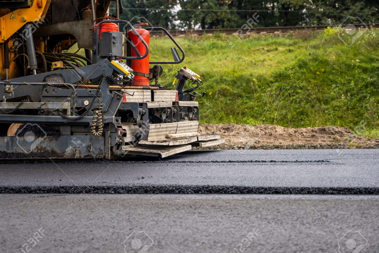 Industrial asphalt paver machine laying fresh asphalt on road construction site. - 159662892