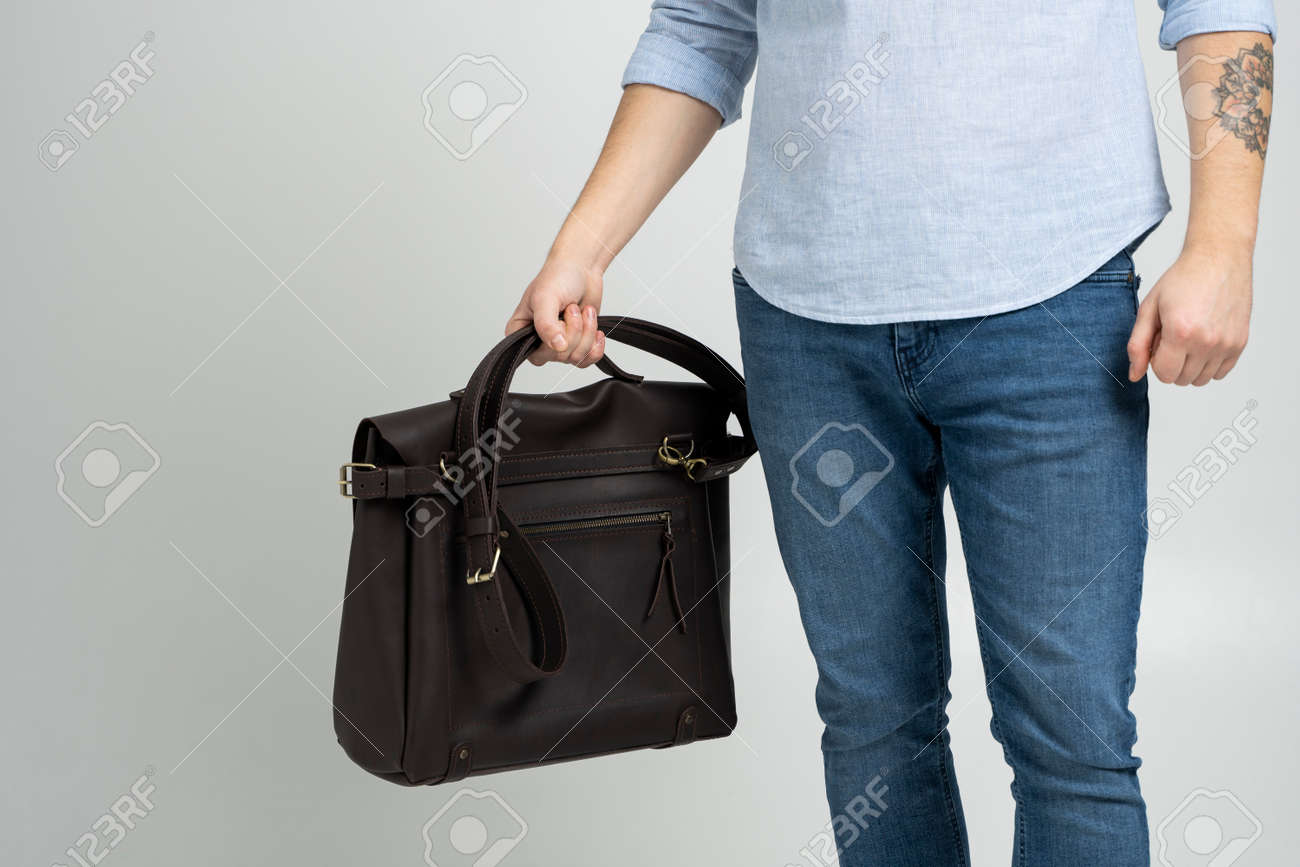 Brown mens shoulder leather bag for a documents and laptop holds by man in a blue shirt and jeans with a white background. Satchel, mens leather handmade briefcase. - 162437853