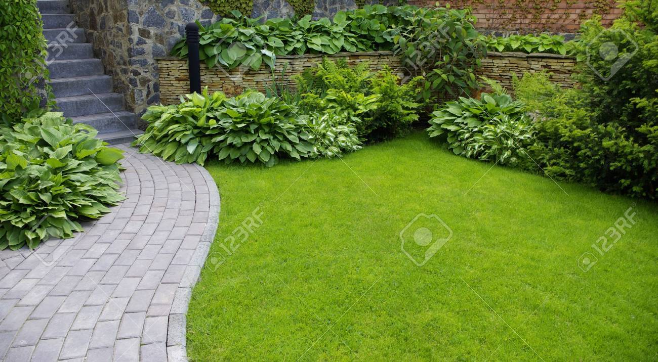 stone garden garden stone path with grass growing up between the stones stock photo