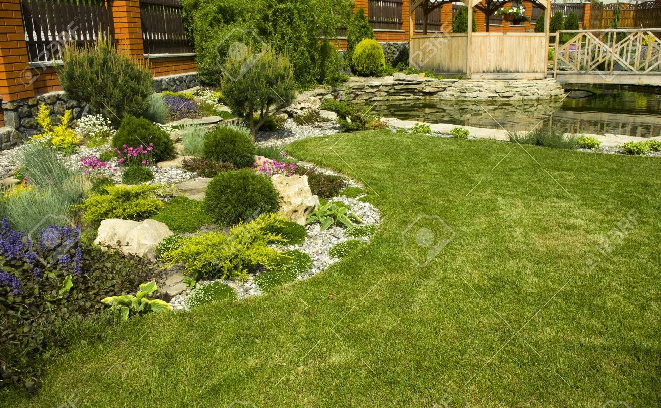 Image De Parterre De Fleurs arbor dans le jardin avec parterre de fleurs, plantes colorées et étang