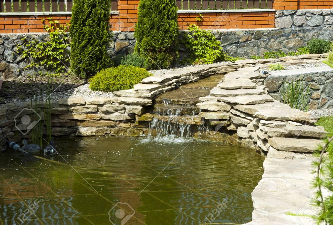 Jardin botanique avec une petite cascade et un étang