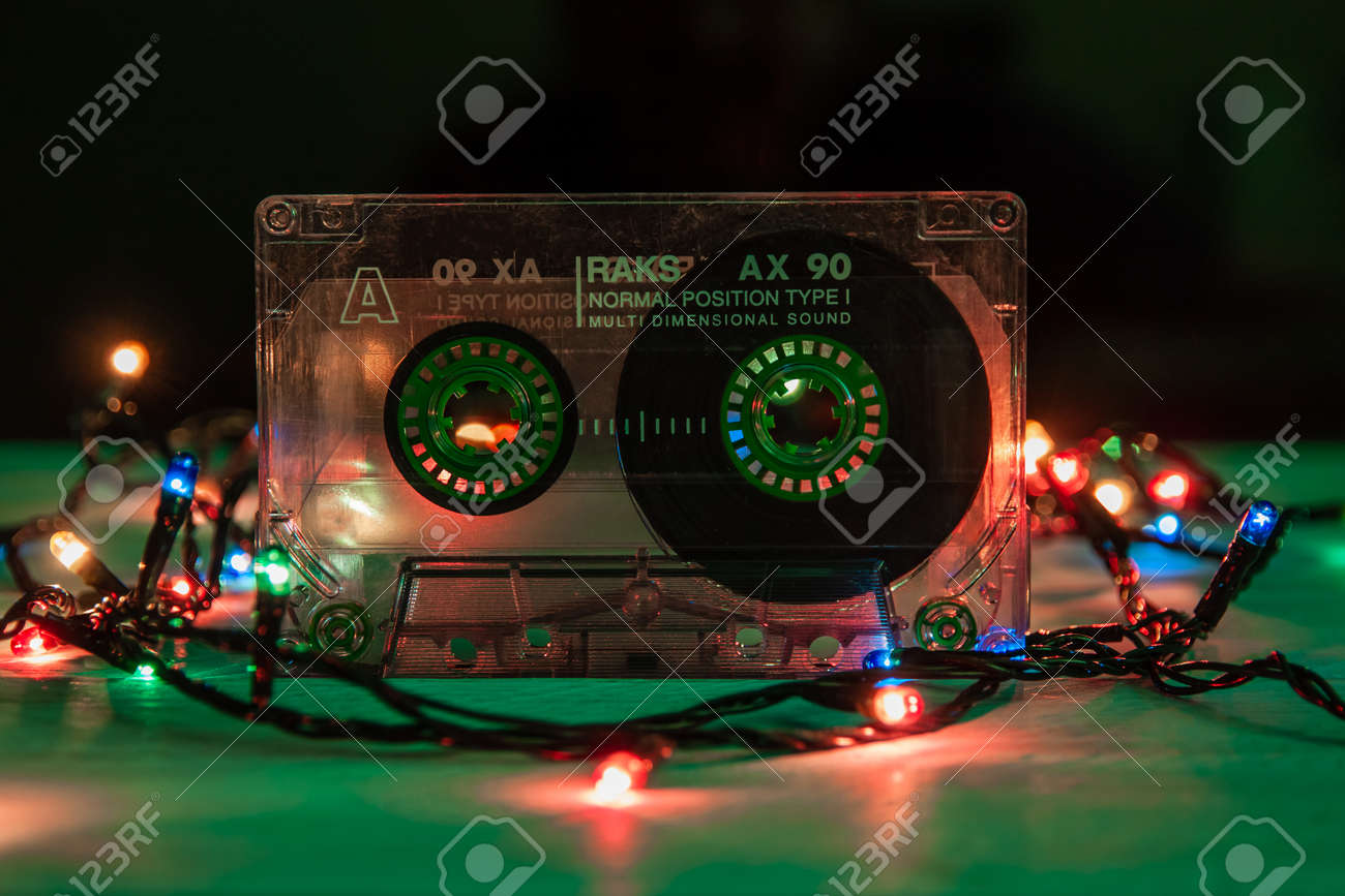 Krasnodar, Russia - March 11, 2021: An old, scratched RAKS audiotape stands on a green background, festooned with multicolored lights. Close-up - 170598382