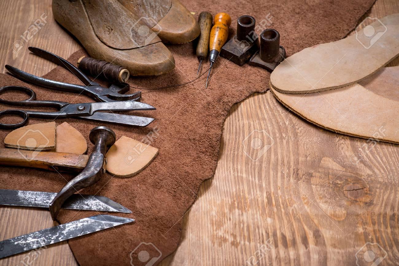 f381beb6f670 Conjunto de herramientas de artesanía de cuero en el fondo de madera. Lugar  de trabajo para zapatero. Pedazo de cuero hechas a mano y las ...