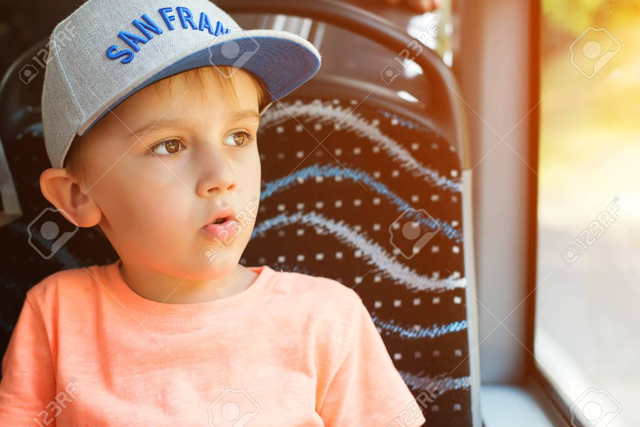 Stock Photo - Surprised boy looking out window of bus. Cute little boy in  cap sitting in bus. Travel 2dca9b5fd5fa