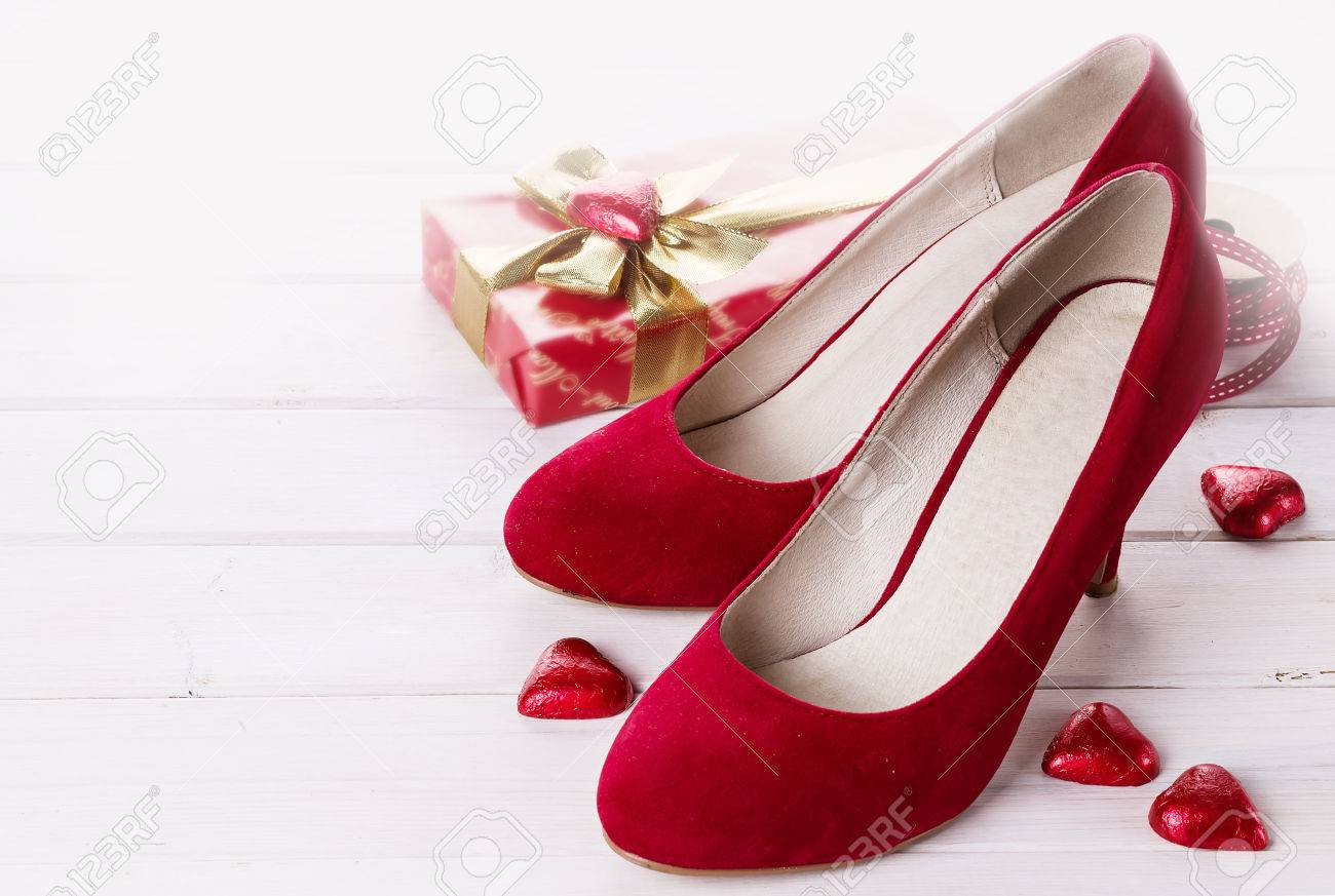 Valentine day items , pair of red shoes, gift box and red chocolate..