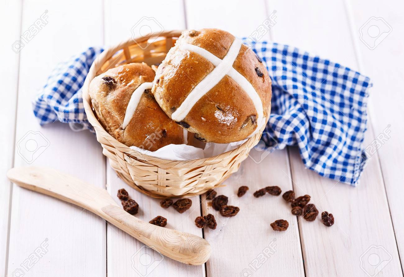 Easter Cross Buns In A Rustic Woven Basket On White Wooden Background Stock Photo
