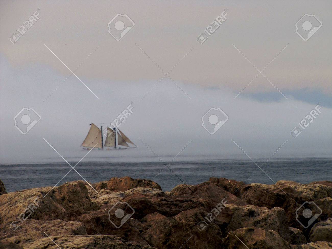 A majestic sailboat drifting through the mist on Traverse Bay - 34435121