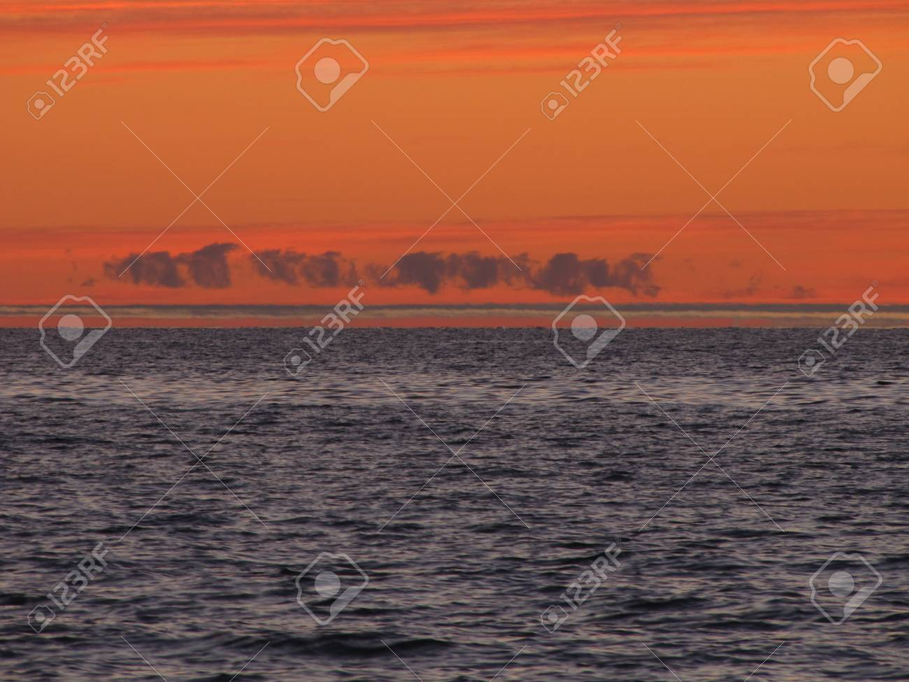 A trail of clouds over Lake Michigan during sunset - 34435178