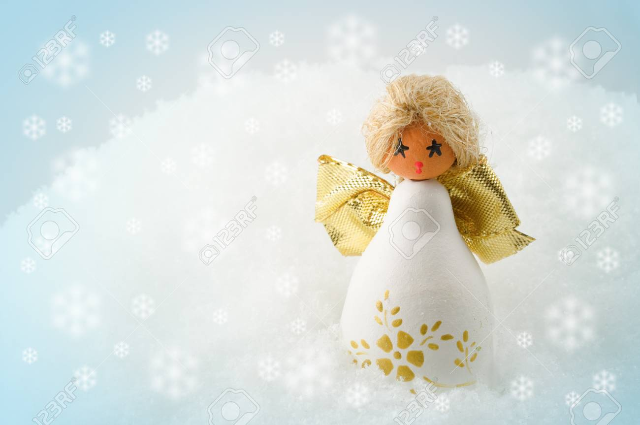 Little cherub with golden wings standing in snow Stock Photo - 11126101