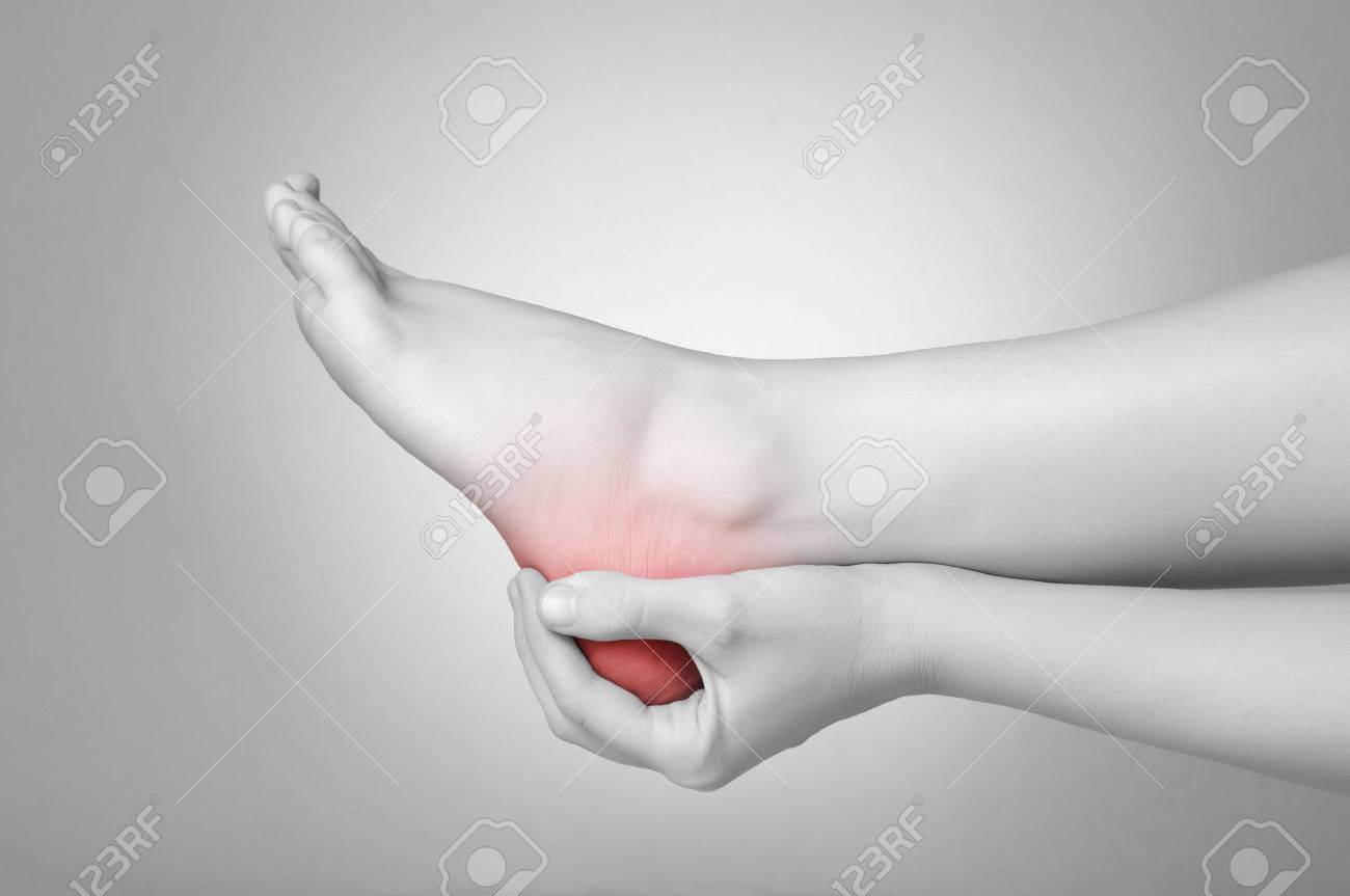A young woman massaging her painful heel Stock Photo - 26018320
