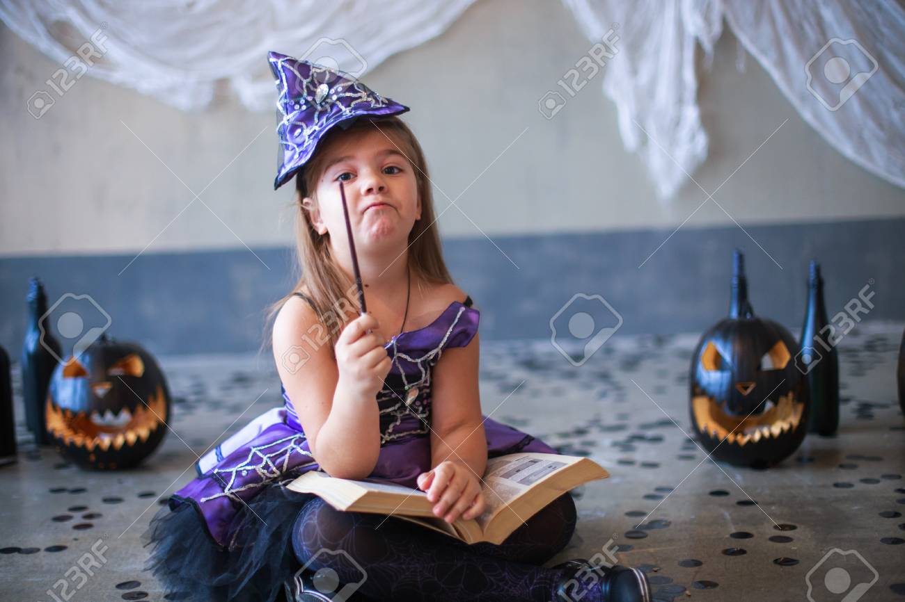 4c8bc830df7c Swing the magic wand. Dressed in a carnival girl. Carnival costume of a  witch. Witch's Hat. child suggests paying attention. girl in the witch  costume ...